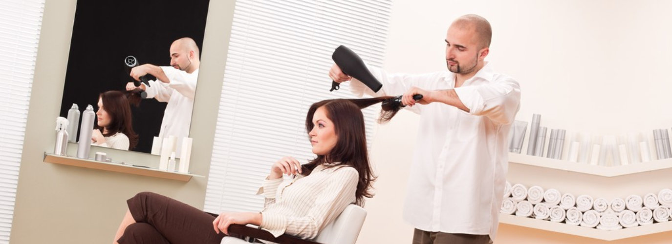 a professional male hairdresser with hair dryer and hair brush working with female customer